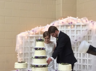 Emily Anderson Hall and Cody Hall cutting their wedding cake