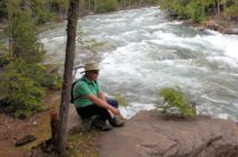 Phil sitting by McDonald Creek rapids