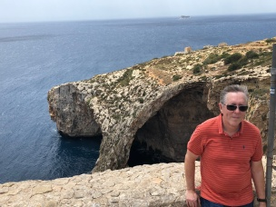 Windblown Phil overlooking Blue Grotto with Filfal Island in background