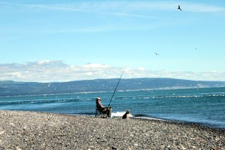 Lonely fisherman and his dog