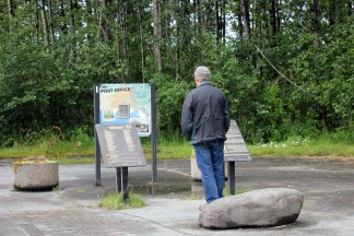 Phil at site of old Valdez post office with plaque listing those who died in Good Friday 1964 earhtquake