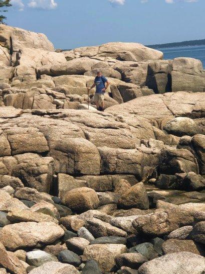 Phil climbing rocks on shoreline trail
