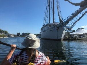 Paddling past sailboat in marina