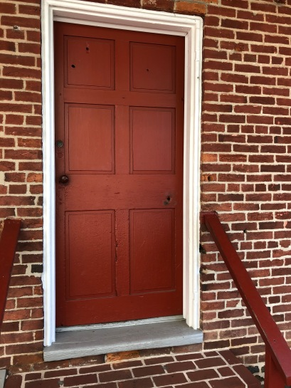 Entry door with hole from bullet that struck Jennie Wade